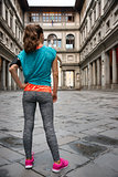 Full length portrait of fitness woman standing in front of uffiz