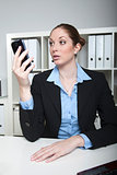 Businesslady looks at her smartphone