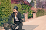 Businesswoman on a Bicycle Calling on her Phone