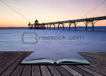 Beautiful long exposure sunset over ocean with pier silhouette c