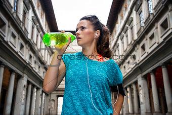Fitness woman drinking water near uffizi gallery in florence, it