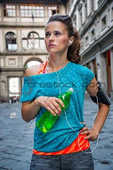 Fitness woman with bottle of water near uffizi gallery in floren