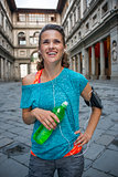 Happy fitness woman with bottle of water near uffizi gallery in
