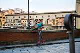 Fitness woman jogging near ponte vecchio in florence, italy