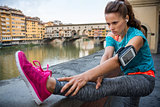 Fitness woman stretching near ponte vecchio in florence, italy