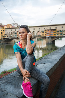 Fitness woman sitting near ponte vecchio in florence, italy and