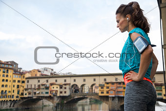 Thoughtful fitness woman standing in front of ponte vecchio in f