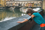 Fitness woman catching breathe in front of ponte vecchio in flor
