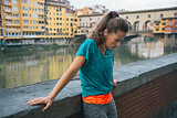 Tired fitness woman in front of ponte vecchio in florence, italy