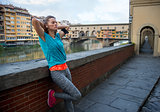 Relaxed fitness woman in front of ponte vecchio in florence, ita