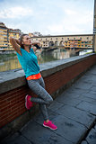 Full length portrait of relaxed fitness woman in front of ponte
