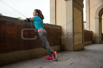 Fitness woman standing outdoors in the city