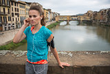 Fitness woman listening music in front of ponte vecchio in flore