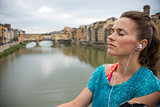 Relaxed fitness woman listening music in front of ponte vecchio