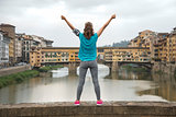 Fitness woman rejoicing in front of ponte vecchio in florence, i