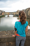 Fitness woman looking on ponte vecchio in florence, italy. rear