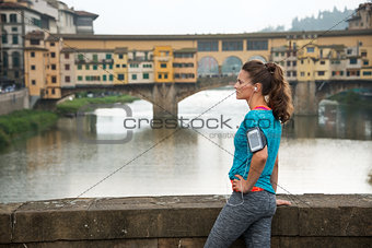 Fitness woman standing in front of ponte vecchio in florence, it