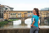 Smiling fitness woman standing in front of ponte vecchio in flor