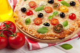 Italian pizza with cheese, tomatoes and basil
