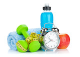 Two green dumbells, tape measure, healthy food and alarm clock