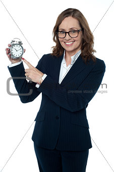 Corporate executive pointing towards the clock