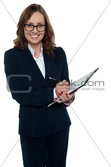 Corporate woman in eyeglasses writing on clipboard