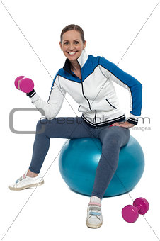 Fit woman doing biceps exercise with pink dumbbells