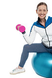 Cheerful woman seated on pilates ball and exercising