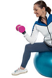 Woman on swiss ball working out with dumbbells