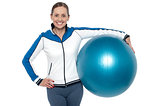 Pretty woman holding big blue pilate ball
