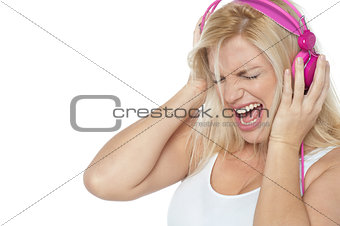 Blonde screaming while listening to rock music