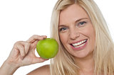 Closeup shot of a cheerful woman holding an apple