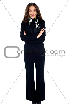 Smiling air hostess standing with arms crossed