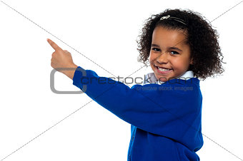 Adorable African kid pointing at copy space area