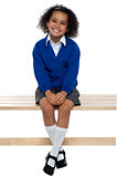 Pretty school girl seated comfortably on a bench
