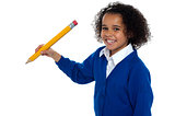 Pretty school kid facing camera with pencil in hand