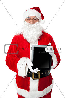 Old man in santa costume posing with a tablet pc