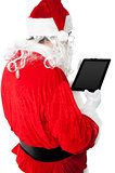 Back view of Santa looking at tablet device screen