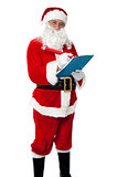 Santa Claus making list of gift recipients