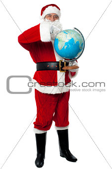 Santa pointing out a continent on globe