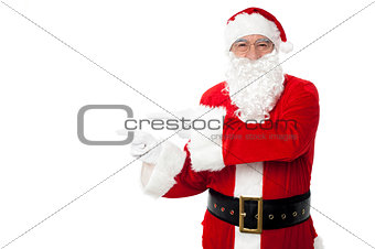 Santa pointing at blank copy space area