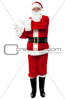 Man in Santa costume indicating at copy space area
