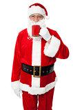 Aged smiling Santa enjoying his coffee