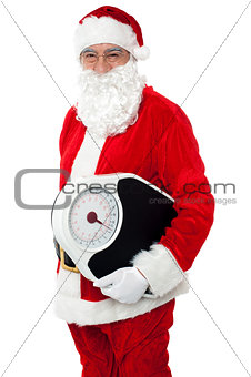Aged male Santa holding weighing scale