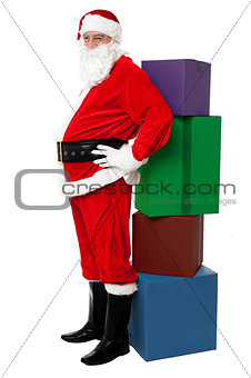Santa leaning over colorful pile of Xmas presents