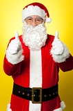 Cheerful male in Santa costume showing double thumbs up