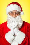 Thoughtful Santa Claus wearing eyeglasses