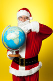 Father Christmas showing his country on globe