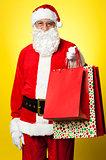 Joyous Santa posing with colorful shopping bags