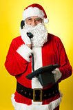 Smiling aged Santa attending phone call